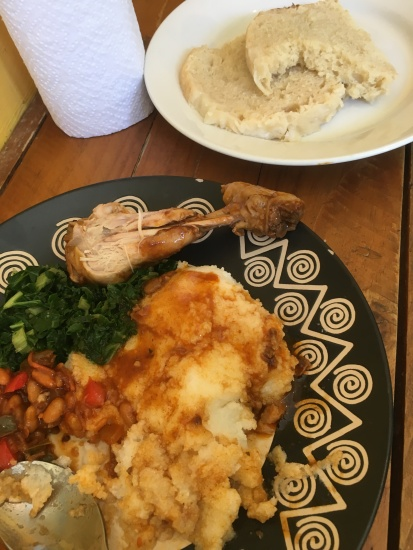 Very traditional meal including a drumstick, pap with gravy, chakalaka, kale, and steamed bread.